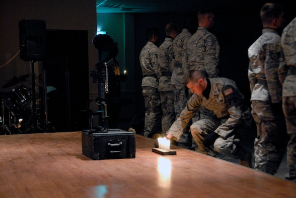 1st Lt. Gregory DeGruchy places a candle in front of a memorial during a candlelight vigil May 13 at an air base in Southwest Asia. The candlelight vigil was a memorial service designated to pay homage to law enforcement officers who selflessly gave their lives in the line of duty during the past year including Air Force Office of Special Investigation special agents, security forces members and military working dogs. Lieutenant DeGruchy is the 386th Expeditionary Security Forces Squadron officer in charge of force protection. (U.S. Air Force photo/Capt. Jason McCree)