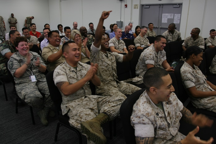 Service members and civilian employees laugh and cheer for Stevie during the Stevie Springer Show. The show was a skit performed by Steve Verret during a driving safety brief May 22 at the Marine Forces Pacific Headquarters Building, Camp H M Smith. Verret is a comedian and traffic safety specialist.