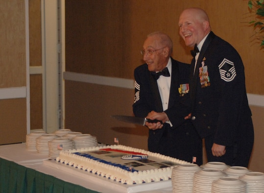 Retired Chief Master Sgt. Gino Conti and Senior Master Sgt. James McCarty, the most senior and junior ranking chiefs in attendance, cut the cake at McCarty's recognition ceremony Wednesday after dinner. (U.S. Air Force photo by Airman Josh Harbin)