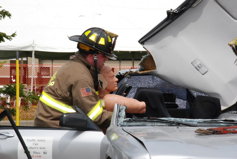 A firefighter from the Frontier Volunteer Fire Company, Wheatfield, N.Y. rescues a mannequin from a vehicle after using the Jaws of Life to open the vehicle.  The vehicle was part of a crash demonstration for the traffic safety program here May 16.  (Photo by Staff Sgt. Rebecca Kenyon).