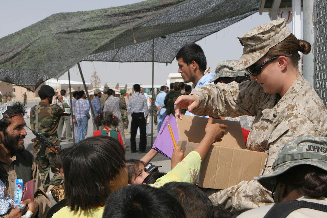 Navy Lt. Dana Cash, medical officer, Combat Logistics Battalion 24, 24th Marine Expeditionary Unit, hands out health care items to Afghan children at Camp Hero, Afghanistan.  Humanitarian aid is an essential function of the CLB while deployed.