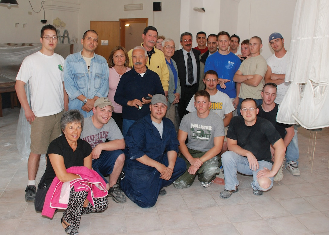 Airmen from the 31st Munitions Squadron at Camp Darby, Italy, and veterans of the Italian Folgore Parachutist Brigade take a break during the refurbishing of the Associazione Nazionale Paracadutisti D'Italia meeting hall in nearby Livorno. (U.S. Air Force photo/Joyce Costello)