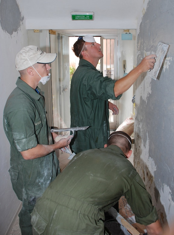 Airmen replaster a wall during a volunteer effort to refurbish an Italian veterans hall in Livorno, Italy.  The Airmen are with the 31st Munitions Squadron at nearby Camp Darby.   (U.S. Air Force photo/Joyce Costello)