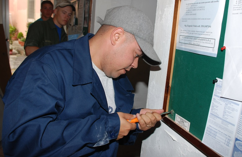 Staff Sgt. Ivan Vallejo prepares to remove a bulletin board during a volunteer effort to refurbish an Italian veterans hall in Livorno, Italy.  Sergeant Vallejo is with the 31st Munitions Squadron at nearby Camp Darby.   (U.S. Air Force photo/Joyce Costello)