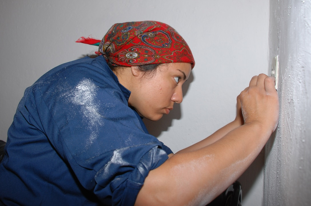 In the spirit of Rosie the Riveter, Airman 1st Class Jennifer Reiff concentrates on prepping a wall for painting during a volunteer effort to refurbish an Italian veterans hall in Livorno, Italy.  Airman Reiff is with the 31st Munitions Squadron at nearby Camp Darby.   (U.S. Air Force photo/Joyce Costello)