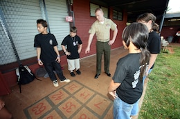 Students with Pearl City Elementary School teach Sgt. Ian Manion, the operations chief for Headquarters and Service Battalion, U.S. Marine Corps Forces, Pacific, how to play hopscotch May 27 outside the school's cafeteria. Manion and three other MARFORPAC Marines received Certificates of Appreciation for volunteering at the school throughout the year.