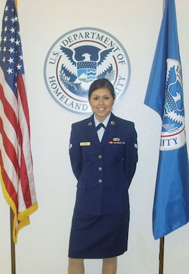 Airman First Class Nimsi Garza, a lodging technician with the 507th Air Refueling Wing Services Flight stands with pride beside the U.S. flag immediately after becoming a U.S. citizen.