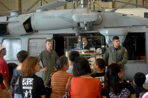 Lt. Quincy Hochard and Petty Officer Second Class Salcavatore Falcone of the Helicopter Sea Combat Squadron-25 present a rescue demo to children and parents from the Big Brothers Big Sisters program of Guam on May 24 here.  The Big Brothers Big Sister program of Guam toured HSC-25, the 734th Air Mobility Squadron, a U.S. Air Force C-17 Globemaster and C-5 Galaxy. (U.S. Air Force photo by Airman 1st Class Courtney Witt)