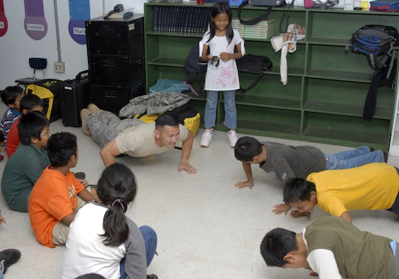 Technical Sgt. Maxwell Pontenila part of the 36th Services Squadron, show Mrs. Herrera's third grade class a correct military push-up.  Sgt. Pontenila was one of five military members speaking to the class about the importance of school, and the importance of starting your education off correctly. (U.S. Air Force photo by Staff Sgt. Patrick Mitchell)