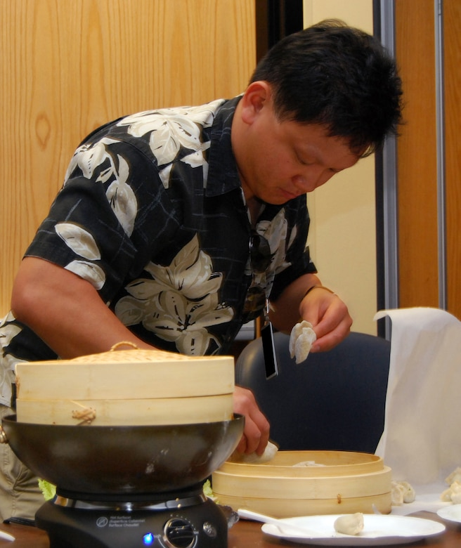 SCHRIEVER AIR FORCE BASE, Colo. -- Capt. Daniel Lee steams dumplings for an Asian-American/Pacific Islander Heritage Month celebration in the Building 300 Auditorium here May 29. Captain Lee used a family recipe to prepare the dumplings, which included pork, spinach and soy sauce. Traditional dumplings are often made with cabbage and can be steamed, boiled or fried. Captain Lee is assigned to the 50th Operations Group's Operational Wing Transition Team here. (U.S. Air Force photo/Staff Sgt. Don Branum)