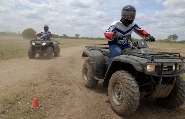 Staff Sgt Robert Carpenter (front), 97th Security Forces Squadron, Altus Air Force Base, Okla., and Staff Sgt Kevin Myers (back), 17th Security Forces Squadron, demonstrate safe riding practices by wearing proper safety gear during the ATV Rider Course May 16. (U.S. Air Force photo by Senior Airman Kamaile Chan)