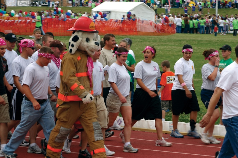 A rowdy crew of Pink Panthers from the 312th Training Squadron walks alongside Sparky the Firedog during the Relay for Life May 16. Pink is the color of cancer awareness. Thirty-two teams from Goodfellow Air Force Base volunteered to walk in the relay, which raised money in the search for a cure. (U.S. Air Force photo by Lt. Col. Terry Smith)