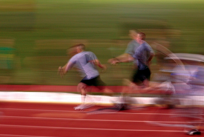 Members of the 344th Military Intelligence Battalion are a blur as they pass their baton during the relay. The Army's A Company ran a total of 500 laps in support of the search for a cure for cancer. (U.S. Air Force photo by Lt. Col. Terry Smith)