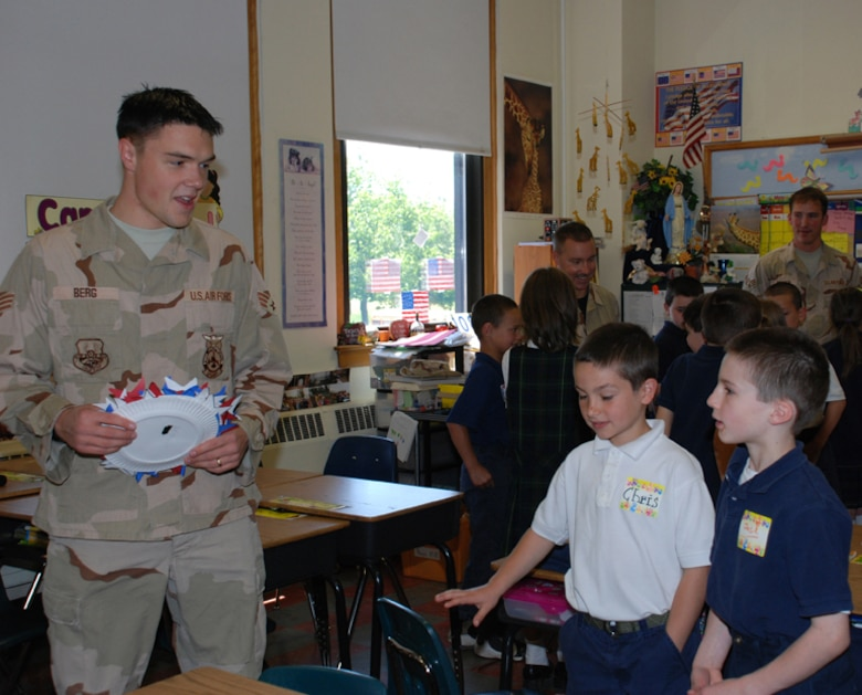 Senior Airman Jason Berg, 107th AW firefighter, talks to his pen pals, Chris and Jack, two second graders from St. Christophers elementary school who wrote to the airman while he was serving in Iraq.  Berg's pen pals presented him with patriotic artwork and thank you cards.