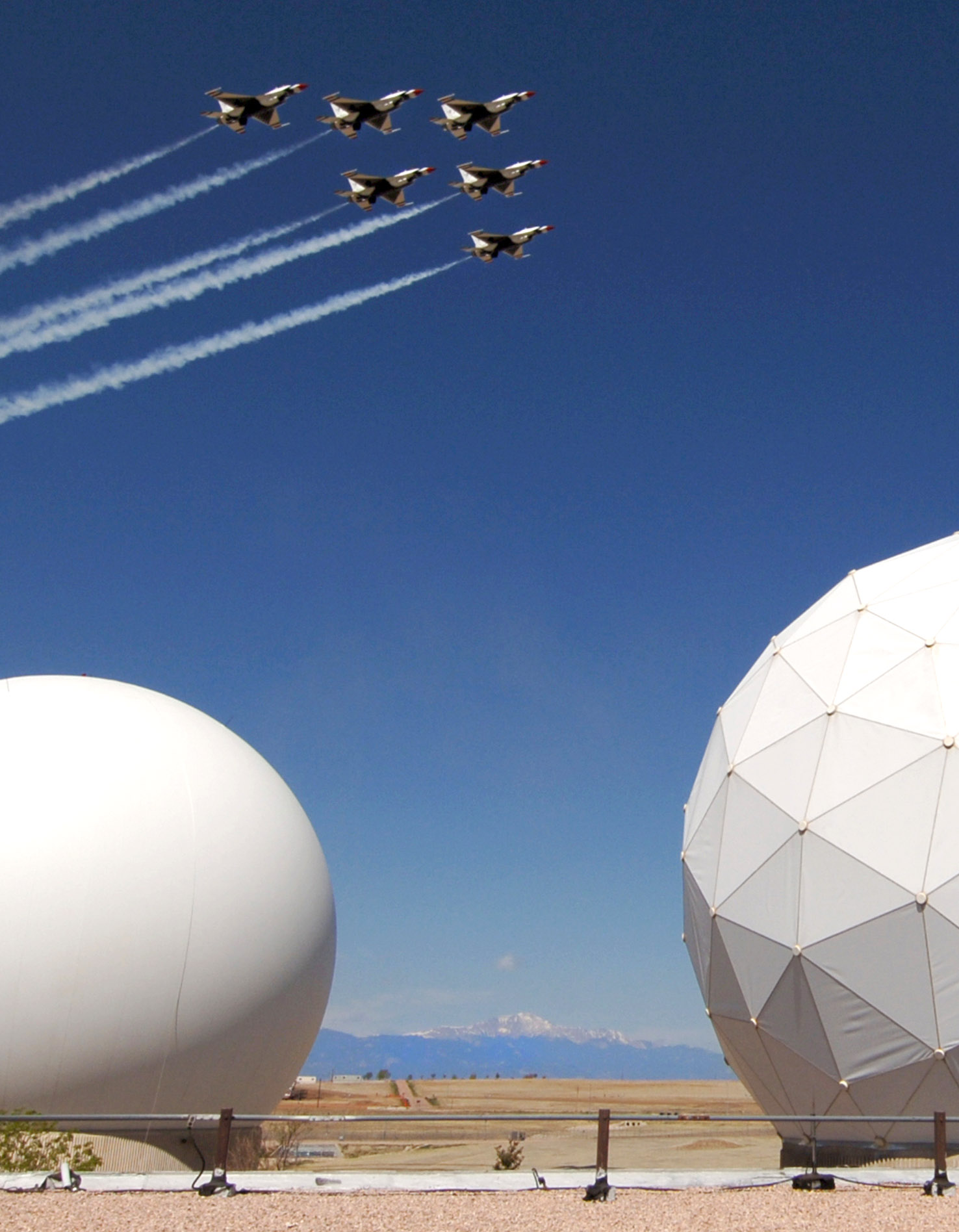 Six military fighter airplanes fly in tight formation over the large, spherical structures containing Schriever's radar arrays. A snow-capped Pike's Peak can be seen in the distance beyond an arid landscape.