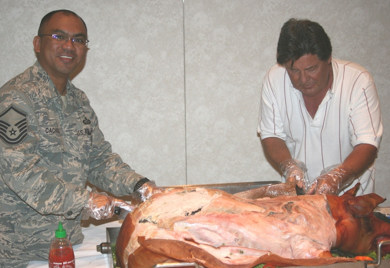"Master Sgt. Alejandro Cachola and Peter Cox, Members of the Asian Pacific Islander Heritage Committee, cut the ""polynesian style"" pig during the 2008 Asian / Pacific Islander Heritage Luncheon May 21. (U.S. Air Force photo by Rogerio Walcott)"