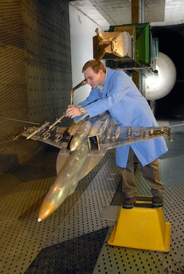 Adam Burt, a co-op student working with Aerospace Testing Alliance, inspects the 1/10-scale models of the sting-mounted AIM-120C store and F/A-18E/F aircraft during a break in store separation testing inside AEDC's 16-foot transonic wind tunnel. ATA is the support contractor for the center. The ongoing testing marks the 13th entry of the Super Hornet for store separation testing in 16T. The data from the testing goes into a database and leads to flight testing. (Photo by David Housch)