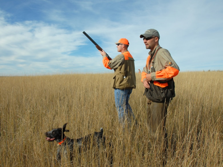 An airman from the 119th Wing prepares to take aim at a flushing rooster pheasant, as Benjamin Sand and his German Wirehaired Pointer, Amber, assist him in his pursuit of upland game birds on the grassy prairies of southwestern North Dakota.