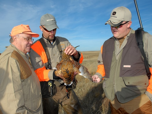 From left to right, Tweed Roosevelt, the great-grandson of twenty-sixth President of the United States Theodore Roosevelt, hunting-dog handler Benjamin Sand, of Bismarck, and Spc. Nathan McGough, of the 231st Brigade Support Battalion, admire a rooster pheasant during the Hunting Dakota with Roosevelt hunt Oct.18 south of Mandan, N.D. McGough beams with pride as the first successful marksman of the day.
