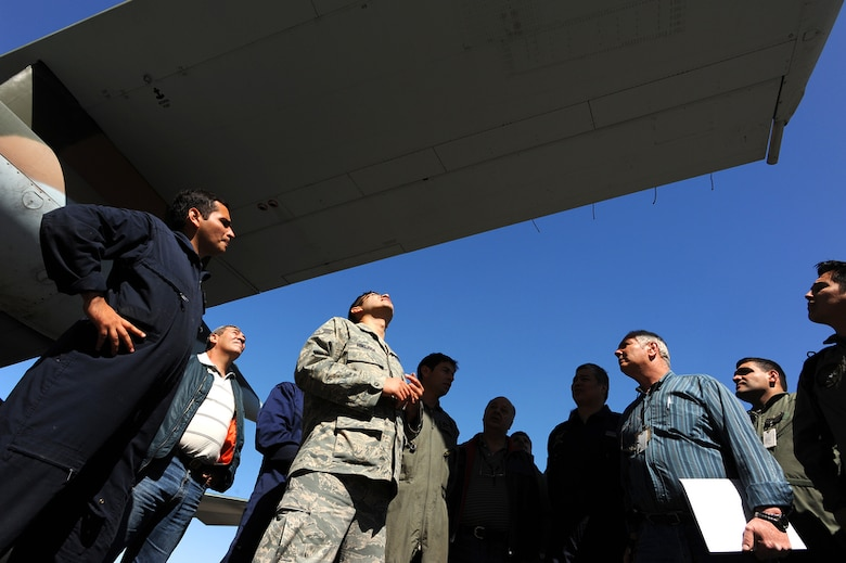 Staff Sgt. David Hinojosa (center) checks for structural damage to Argentinean air force C-130 Hercules' wing during an aircraft maintenance evaluation at Palomar Air Base, Buenos Aires, Argentina during Operation Southern Partner Oct. 30. Operation Southern Partner is an in-depth, two-week subject matter exchange emphasizing partnership, cooperation and sharing of information with partner nation Air Forces in Latin America. Staff Sgt. Hinojosa is an aircraft structural maintenance instructor for the Inter-American Air Force Academy at Lackland Air Force Base, Texas.(DMA-SA photo/Staff Sgt. Bennie J. Davis III)