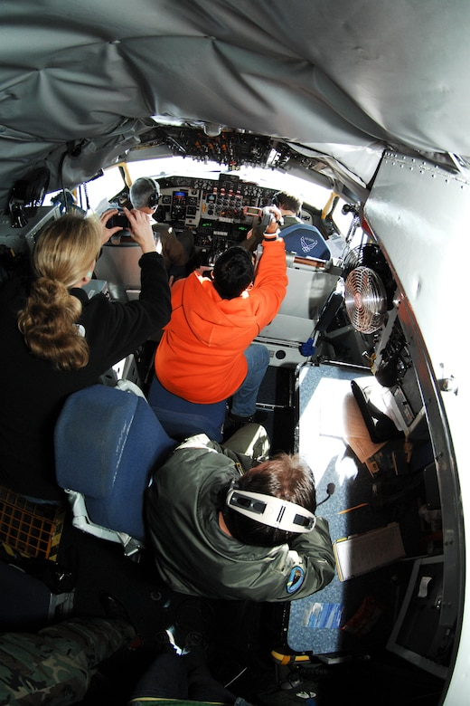 Dessie Sudberry (top middle), takes photos behind the cockpit of a KC-135 Stratotanker while Master Sergeant Johnny White (bottom right), boom operator with the 171st Air Refueling Squadron, observes. The flight served to familiarize 127th Air Refueling Group spouses with the new air refueling mission of the 127th Wing. (U.S. Air Force photo by Senior Airman Jeremy L. Brownfield) (Released)