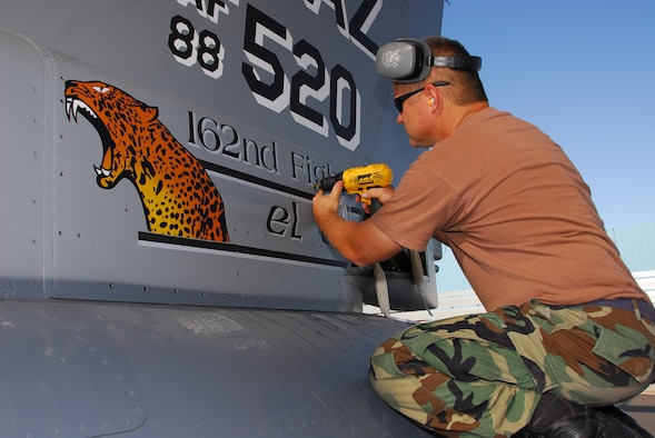 """Tech. Sgt. Rick Bain attaches a freshly-painted tailflash to the 162nd Fighter Wing commander's F-16 on the flightline here Nov. 1. The panel features the unit mascot """"El Tigre,"""" a jaguar native to the Sonoran desert. The roaring """"tigre"""" was painted by Staff Sgt. Aaron Roop, a structural maintainer, and designed by Senior Airman Jonathan Rojas, a graphic artist assigned to the wing public affairs office. (Arizona Air National Guard photo by Senior Airman Sarah Elliott)"""