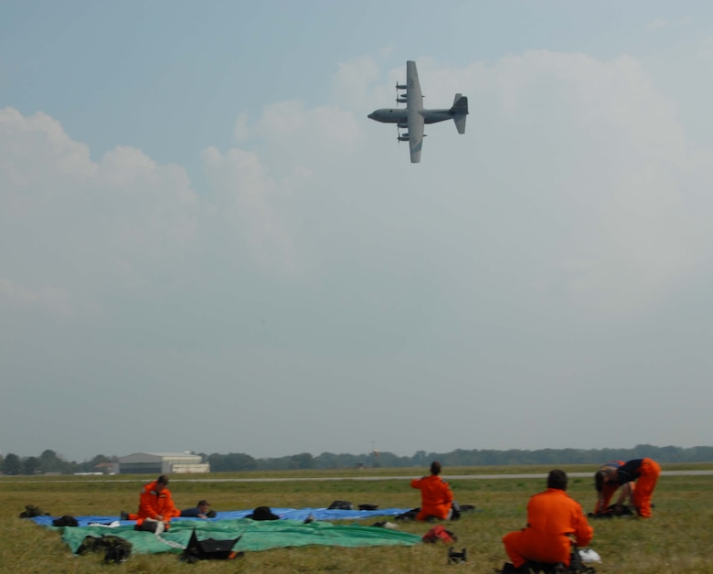 A Kentucky Air Guard C-130 Hercules aircraft banks above rodeo participants at Fort Knox, Ky.