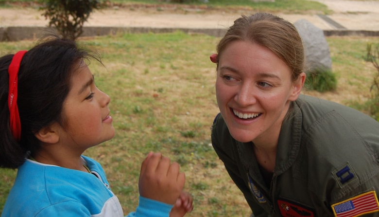 Capt. Becky Russo is all smiles after recieving a flower Oct. 31 from a Chilean girl during a visit to ALDEAS SOS orphanage in Quilpué, Chile. Captain Russo, a C-17 Globemaster III aircraft commander from the 535th Airlift Airlift Squadron at Hickam Air Base, Hawaii, visited the orphanage while on a community outreach program during Operation Southern Partner, a Twelfth Air Force (Air Forces Southern) led event aimed at providing intensive, periodic subject-matter exchanges in the U.S. Southern Command area of focus. (Air Force photo/Master Sgt. Eric M. Grill)