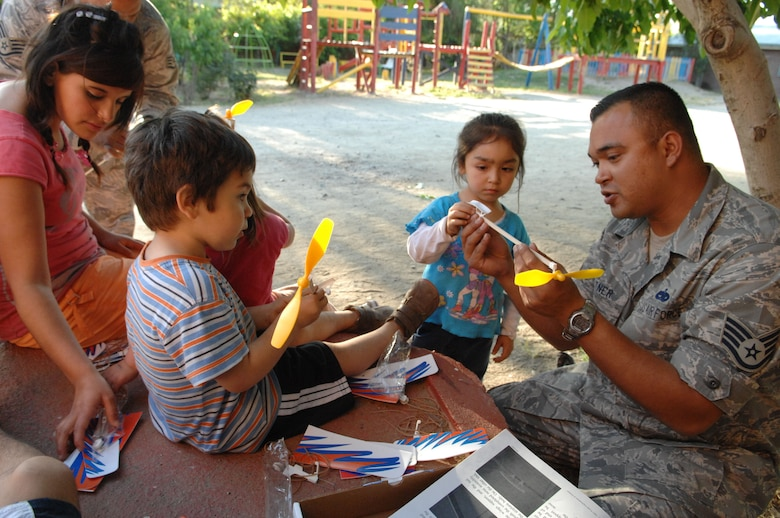 Staff Sgt. Lee Fortner, an aircraft maintainer from the 355th Maintenance Group at Davis Monthan Air Force Base, Ariz., demonstrates how to build a model airplane to orphans at a Santiago, Chile orphanage on Oct. 30. Sergeant Fortner is one of about 70 Airmen spread across four South American countries learning and sharing with their partner nations' military members and performing community outreach events as part of Operation Southern Partner -- a Twelfth Air Force (Air Forces Southern) led event aimed at providing intensive, periodic subject-matter exchanges in the U.S. Southern Command area of focus. (Air Force photo/Tech. Sgt. Roy Santana)