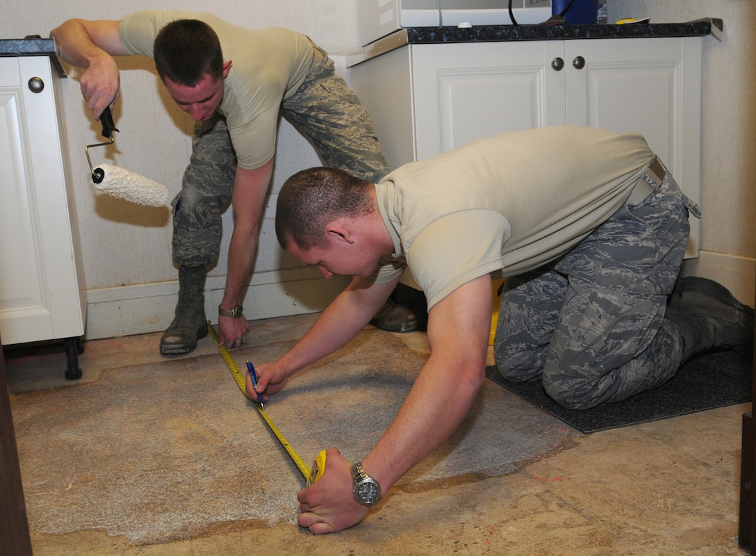Airman Cody Seymour and Airman Scott Ricketts, both from the 100th Civil Engineer Squadron Structures Shop, measure and mark out the position for carpet tiles on the floor of the kitchen area in the 100th Air Refueling Wing headquarters building Oct. 29. The structures shop personnel are responsible for maintaining buildings on base and their job includes dealing with roof leaks, replacing doors, and the overall structural integrity of buildings. (U.S. Air Force photo by Karen Abeyasekere)