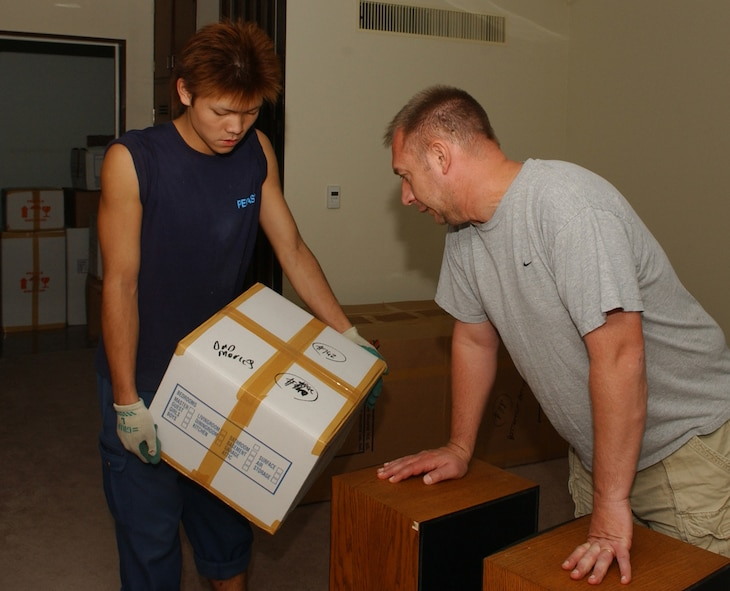 Senior Master Sgt. Timothy Petersen, 374th Airlift Wing command post, tells Mr. Tagami Hiroku where to place the boxes that he is recieving from his previous base. Sergeant Petersen recently movedd to Yokota and is recieving his house-hold goods and furniture from his prior base. (U.S. Air Force photo by AIrman1st Class Eric Summers)