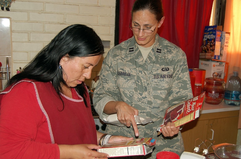 Capt. Anabelle Cabreja translates the directions for baking a cake into Spanish for a housemother Oct. 30 at a home for abused or neglected children near Santiago, Chile. Captain Cabreja is assigned to 12th Air Force at Davis Monthan Air Force Base, Ariz. (U.S. Air Force photo/Master Sgt. Eric M. Grill)