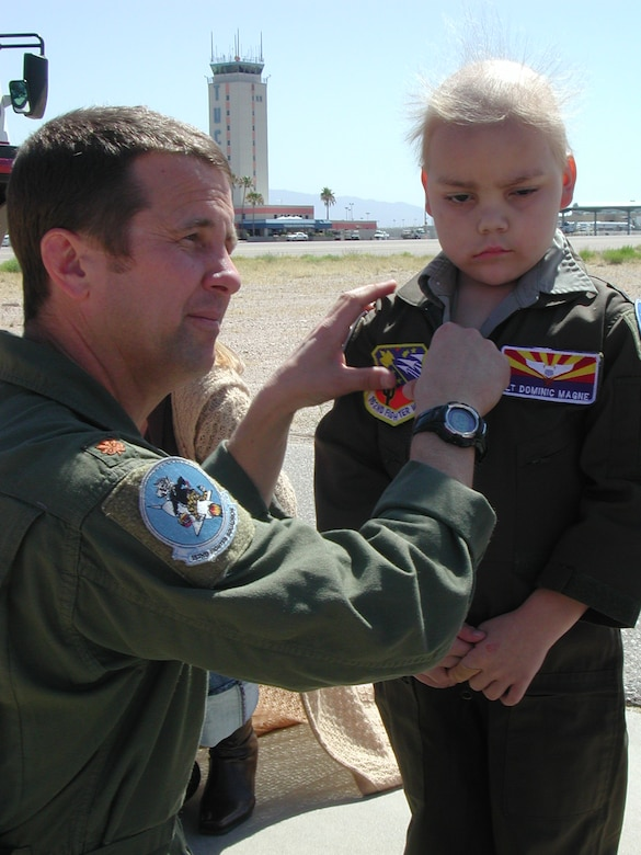 Lt. Col. Scott Reinhold, then a major, puts the 162nd Fighter Wing patch on 6-year-old Dominic Magne's flightsuit during his visit to the Arizona Guard unit April 17, 2007. Dominic, a leukemia patient from Flagstaff, Ariz., was introduced to Colonel Reinhold through Dream Factory, a nonprofit organization that grants dreams to critically ill children. Now an honorary member of the wing, his friendship with Reinhold has grown and his health has improved. (Air National Guard photo by Capt. Gabe Johnson)