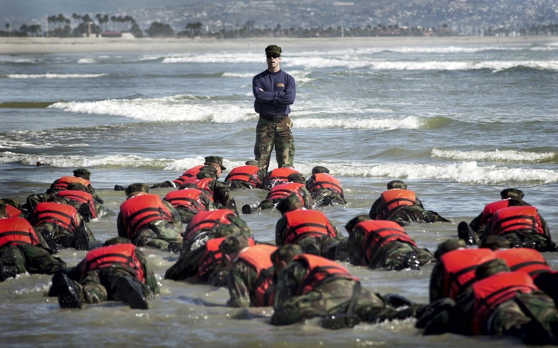 A Navy SEAL instructor watches as BUD/S students participate in surf drill training at the Naval Special Warfare Center in Coronado, Calif. U.S. Navy photo by Petty Officer 2nd Class Eric S. Logsdon