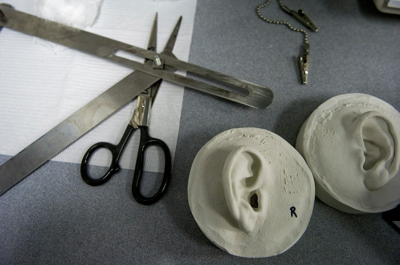 A 3-D model resin prosthesis mold of ears and tools lie on a table at the McGowan Dental Clinic Sept. 29 at Lackland Air Force Base, Texas. Maxillofacial prosthodontists of the 59th Medical Wing create ears, eyes and noses for military members that have been injured during duty. (U.S. Air Force photo/Staff Sgt. Desiree N. Palacios)