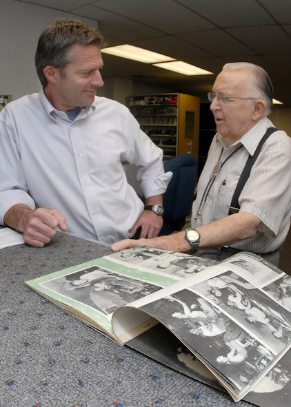 Public Address Lead Gary Thomas and 1st Lt. (ret.) James Spence discuss memories from a 1943 the 35th Photo Tech Unit Yearbook of Guam, where Lieutanant Spence transferred after his assignment at Peterson Field. (Air Force photo/Rob Bussard)
