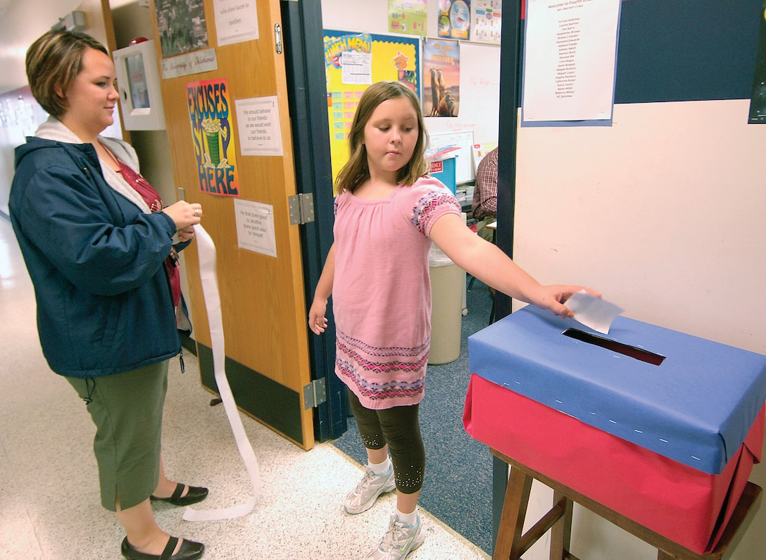 "Tinker Elementary School  fourth-grader Brianna Zenzen casts her vote Oct. 30 for president as teacher Cindy Yarnell readies an ""I voted"" sticker for the student. Many students had strong opinions about their presidential hopeful. Some students had watched every debate, cited reasons for their choices, often picking a candidate opposite their parents' favorite. When the votes were tallied, Barack Obama came out the winner. (Air Force photo/Margo Wright)"
