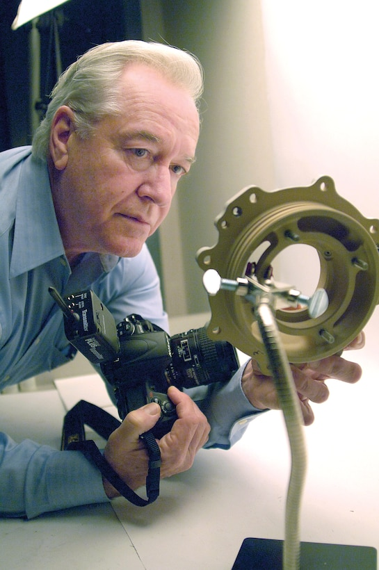 Larry Smith prepares a part before photographing it in the Metallurgical Sciences Laboratory in Bldg. 3001.  The photographer helps Tinker engineers by documenting specifics of new or failed components. During the Vietnam War, Mr. Smith was a private first class with the 2nd Battalion, 9th Marine Regiment, earning two Purple Heart medals.  (Air Force photo/Margo Wright)