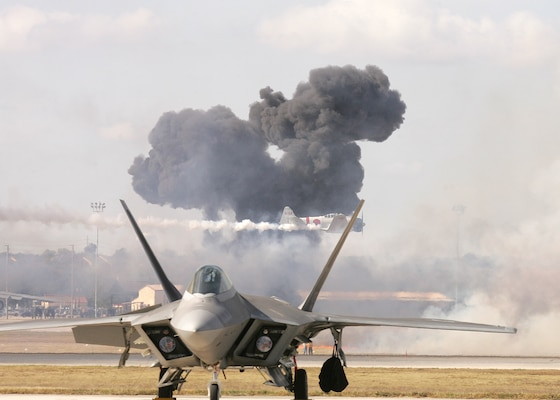 11/1/2008 - The Pearl Harbor reenactment of Tora! Tora! Tora! fills the sky with smoke behind the F-22 Raptor during AirFest 2008 at Lackland Air Force Base, Texas. (USAF photo by Robbin Cresswell)