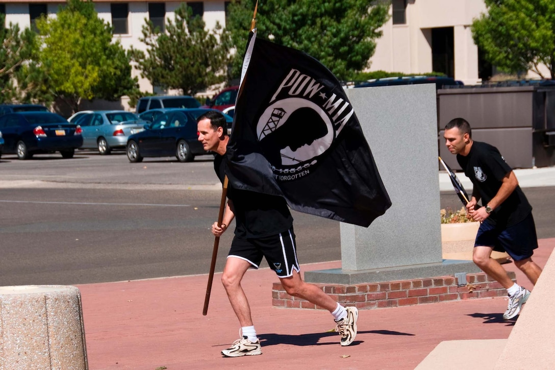 Col. Robert Campbell, Jr., Air Force Operational Test and Evaluation Center Detachment 3 Commander, carries the POW/MIA flag on the inaugural lap of the annual POW/MIA 24-hour run held each September at Kirtland AFB, N.M.