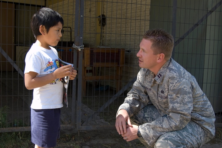 Capt. Nathan Broshear, Twelfth Air Force (Air Forces Southern) Public Affairs, talks to a Chilean child during a visit to the ALDEAS SOS orphanage food exchange in Santiago, Chile where Airmen, a Soldier and U.S. civilian volunteers ate a traditional Chilean lunch. In exchange, the Chileans were treated to a favorite American food – peanut butter and Jelly sandwiches. Captain Broshear and seven other participants are in South America for Operation Southern Partner -- a Twelfth Air Force (Air Forces Southern) led event aimed at providing intensive, periodic subject-matter exchanges in the U.S. Southern Command area of focus. (Air Force photo\Master Sgt. Eric M. Grill)