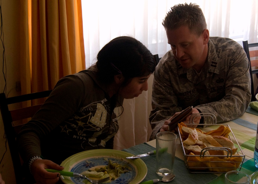 Capt. Nathan Broshear, Twelfth Air Force (Air Forces Southern) Public Affairs, shows a picture to one of the participants at the ALDEAS SOS orphanage food exchange in Santiago, Chile where Airmen, a Soldier and U.S. civilian volunteers ate a traditional Chilean lunch. In exchange, the Chileans were treated to a favorite American food – peanut butter and Jelly sandwiches. Captain Broshear and seven other participants are in South America for Operation Southern Partner -- a Twelfth Air Force (Air Forces Southern) led event aimed at providing intensive, periodic subject-matter exchanges in the U.S. Southern Command area of focus. (Air Force photo\Master Sgt. Eric M. Grill)