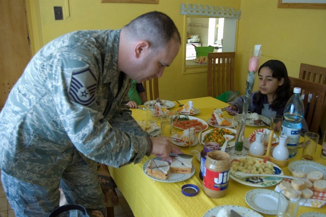 Master Sgt. Eric M. Grill, from the Defense Media Activity-San Antonio in Texas, cuts a peanut butter and jelly sandwich into quarters before serving it to Chilean children at the ALDEAS SOS orphanage in Santiago, Chile on Oct. 29. Sergeant Grill is in South America supporting Operation Southern Partner, a Twelfth Air Force (Air Forces Southern) led event aimed at providing intensive, periodic subject-matter exchanges in the U.S. Southern Command area of focus, started Oct. 26 and ends Nov. 7. (Air Force photo\Dana Willis)
