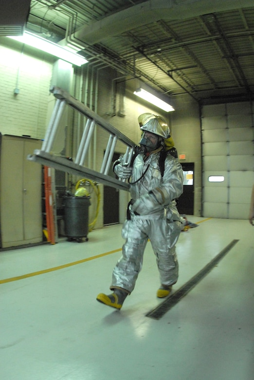 Tech Sgt. Tad R. Brown, a 119th Civil Engineer Squadron fire fighter, carries a ladder during a timed fire fighter fitness test Nov. 6 in the North Dakota Air National Guard fire hall on the east edge of the Hector International Airport runway, Fargo, N.D.  The fitness test is an annual requirement for the fire fighters and includes various obstacles designed to simulate challenges that they might encounter during fire fighting and fire victim rescue attempts.   (NDANG photo by Senior Master Sgt. David H. Lipp) (Released)