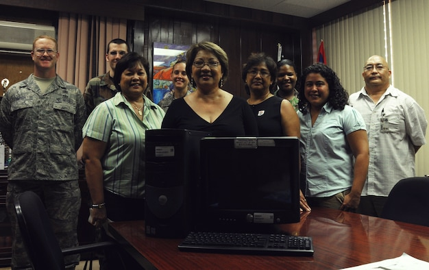 ANDERSEN AIR FORCE BASE, Guam – Posing for a group photo, in the front row, Jane Sasai, 36th Communications Squadron equipment control officer; Narrisa Bretania-Shafer, superintendent; May Camacho, special education administrator; and Christine Rosario, special education assistive technology program coordinator and, in the back row, Master Sgt. Larry Simpson, Airman 1st Class James Morris, Senior Airman Ashley Fears, Tech. Sgt. LaShanda Santiago and Mario Jallorina, all from the 36 Communication Squadron, stand around one of the Dell Optiplex computers donated to local special needs classrooms on Guam, Nov. 4.  (U.S. Air Force Photo by Staff Sgt. Jamie Lessard)