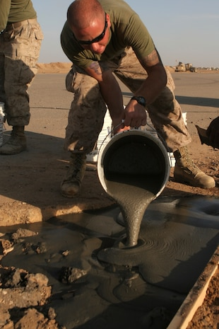 Cpl. Justin S. Sher, a 21 year old combat engineer, Marine Wing Support Squadron 273, pours concrete into a crater caused by erosion on the Camp Sinjar airstrip.  These Marines are repairing the airstrip to make it capable of supporting F/A-18's.  This is also the only Marine run airstrip in the Nineweh province, in support of the Marine Air Ground Task Force participating in Operation Defeat Al-Qaida in the North II.