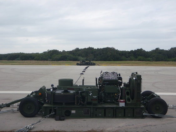 An M-31 Marine Corps Expeditionary Arresting Gear System is installed and ready for use on a runway. Marines with the 2nd Marine Aircraft Wing, based out of Marine Corps Air Station New River, N.C. and 3rd MAW, from MCAS Miramar, Calif. implemented the system for the 2nd Annual Space & Air Show at Kennedy Space Center Nov. 9.