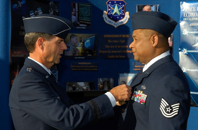 Lt. Gen. John T. Sheridan, SMC commander, presents Tech. Sgt Phillip Barton with the Air Force Commendation Medal at the Air Force Space Command display outside of the Los Angeles Coliseum before the start of the USC football game, Nov. 8. The ceremony was part of the events leading up to Air Force Week in Southern California. Air Force Week serves as the premier platform to share the Air Force story with our fellow citizens. The 2008 Air Force Weeks will include community visits and talks by Air Force officials, flight demonstrations and displays providing an up close and personal look at the men and women of the Air Force serving worldwide in defense of freedom. (Photo by Stephen Schester)