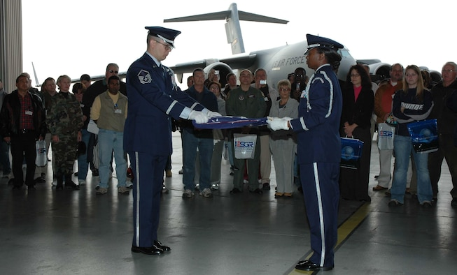 MCGUIRE AIR FORCE BASE, NJ -- Employers watch as Reserve honor guards perform a flag folding ceremony during the 514th Air Mobility Wing's annual Employer Appreciation Day here. The employers also participated in a simulated deployment process that included a flight on a KC-10 Extender or C-17 Globemaster III. (U.S. Air Force photo/SrA. William P. O'Neil III)