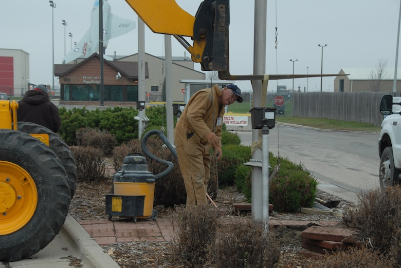 Kieth Anderson of T.F. Powers Construction works at removing flag poles at the current main entrance to the North Dakota Air National Guard.  The flag poles will be moved and placed at the new entrance located north of the base on 32nd Avenue north.